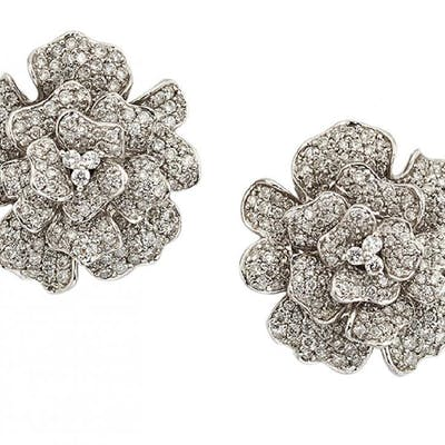 A pair of diamond earrings, of stylised floral design, the undulating