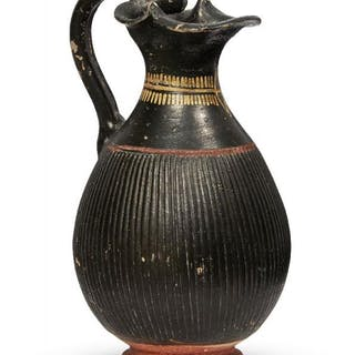 An Etruscan red and black glazed pottery jug with serpent head handle