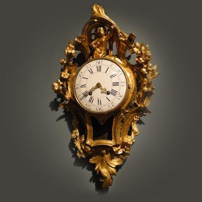 Cartel clock in gilded, cast bronze
