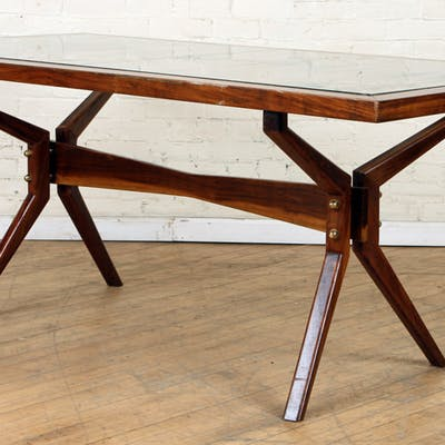 A mid century modern mahogany and glass dining table in...