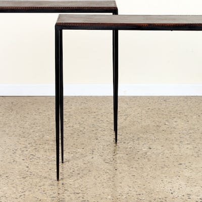 A pair of stitched leather and iron console tables in the...