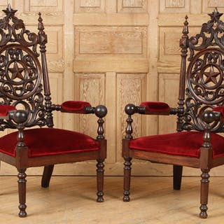A pair of late nineteenth century Gothic oak arm chairs...