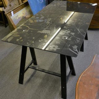 An Ikea black floral design glass table top with black trestle legs