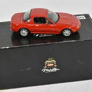A Kyosho 1/18 scale diecast model of a Mazda Miata MX-5, red, with