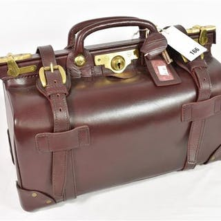 A burgundy leather Penhaligon gladstone bag