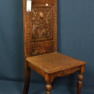 A heavily carved antique oak hall/side chair