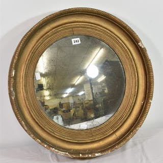 An antique circular gilt and composition framed convex mirror