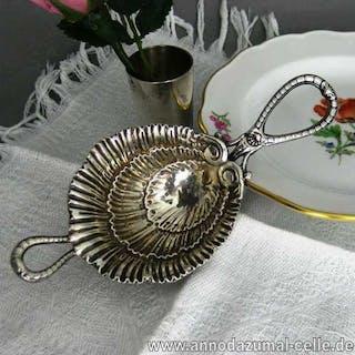 Silberner Teesieb in Form einer Muschel