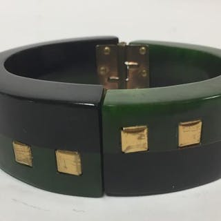 A Bakelite hinged black and green bangle with square brass inlays