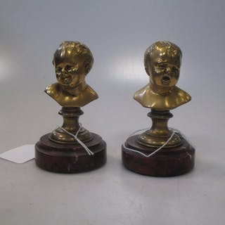 A pair of French gilt bronze busts depicting a laughing child and