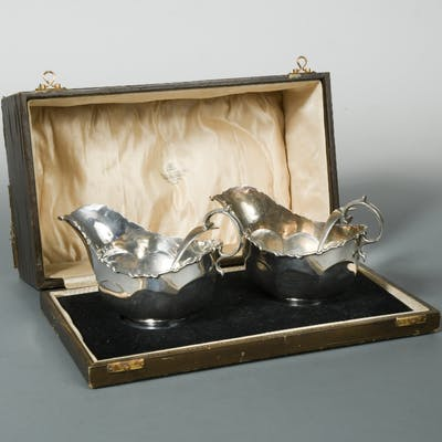A cased pair of George V silver sauce boats with sauce ladles en suite