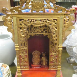 A carved giltwood Oriental shrine with small separate gilt figure and tablet