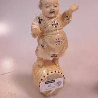 A Japanese ivory okimono, modelled as a young boy standing on a drum