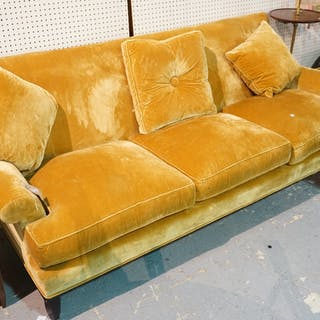 Baker; a modern three seater sofa with gold velvet upholstery, on