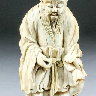 A Chinese carved ivory seated figure of Shoulao of archaic form