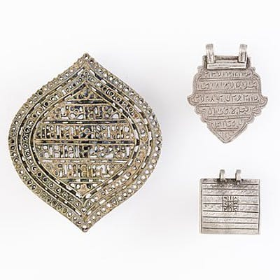 TWO SILVER PLAQUE AMULETS, silver and brass and  BRASS STAMP, North