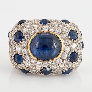 An 18K gold ring set with a cabochon-cut sapphire and round brilliant-cut