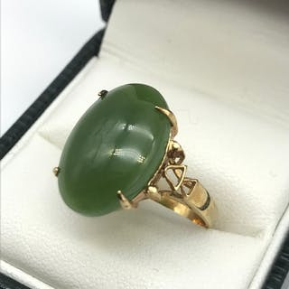 An antique gold ring set with a large oval shaped jade stone...