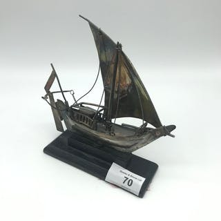 A Silver made model junk boat sat upon a hardwood stand. Mea...