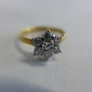 An 18ct yellow and white gold diamond daisy cluster ring, th...