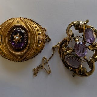 A Victorian gold coloured metal oval brooch set amethyst and...