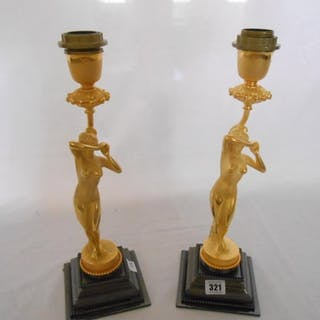 A pair of gilt metal tablelamp bases in the form of nude fem...