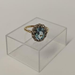 A 9ct. gold ring of cluster form set pale blue centre stone ...