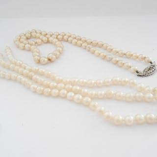 A row of pearls with 18ct. white gold clasp set three stones...
