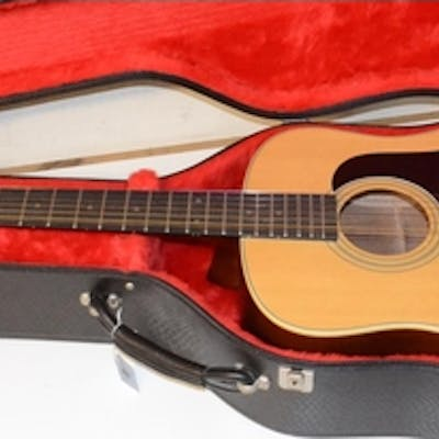 An Aria twelve string acoustic guitar, in a hard case
