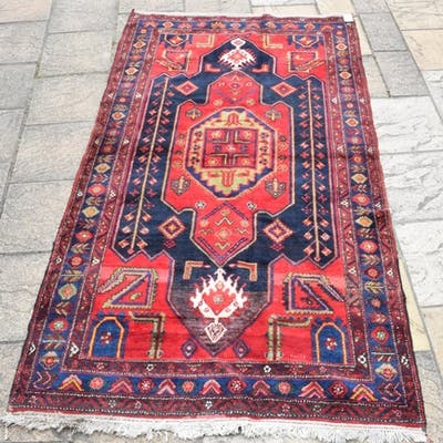 A Persian carpet, the central medallion on a red ground, 273...