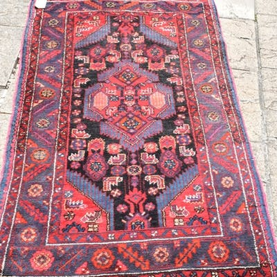 A Persian rug, decorated motifs on a red ground, within a mu...