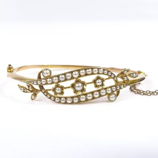 An Edwardian 15ct gold split-pearl floral hinged bangle, set...