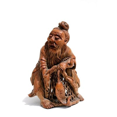 A Chinese carved bamboo figure depicting a fisherman and his...