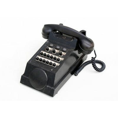 A black Bakelite exchange telephone.