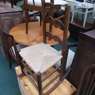 A ladder back rocking chair with a rush seat pad.