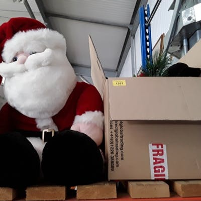 A box of Christmas decorations together with a stuffed Santa...