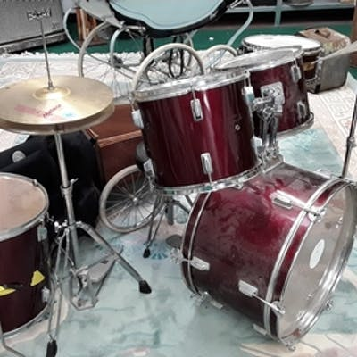 A drum kit with a bag of drum skins.
