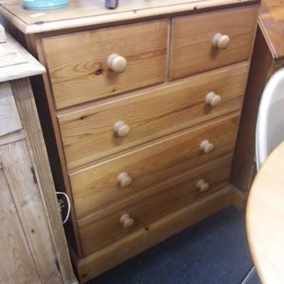 A modern five drawer pine chest.