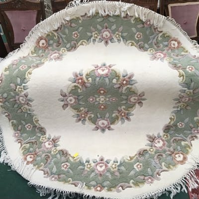 A round floral rug with hand knotted cotton tassels.