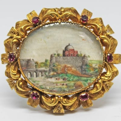 A Victorian yellow metal brooch set with rubies and an India...