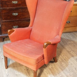A retro Parker Knoll armchair with wing back and show wood a...
