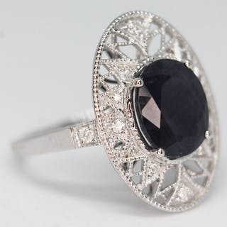 An 18ct gold diamond and sapphire ring, the oval cut Kashmir...