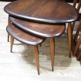 A set of three Ercol elm and beech nest of tables, blue labe...