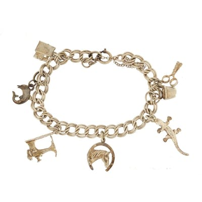 Silver charm bracelet with a selection of mostly silver char...