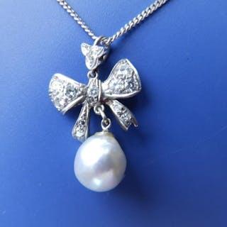 A diamond set white metal ribbon pendant with grey pearl swing on