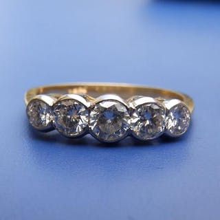 An '18ct' graduated five stone diamond ring with white metal collect