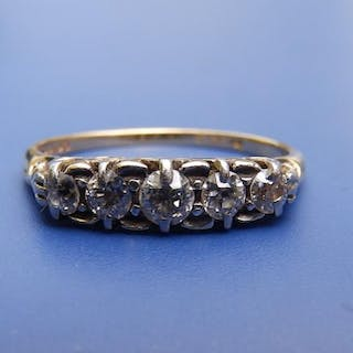 A five stone graduated diamond ring in '18ct' yellow metal. Finger size R/S.