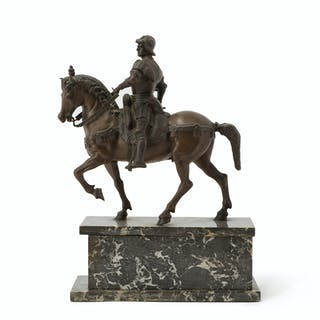A patinated bronze horse and rider