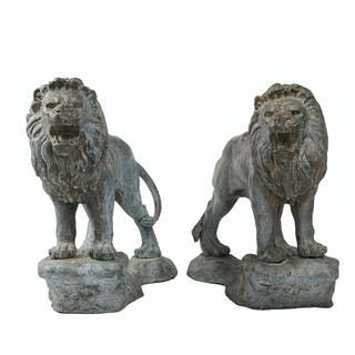 A pair of patinated metal standing lions