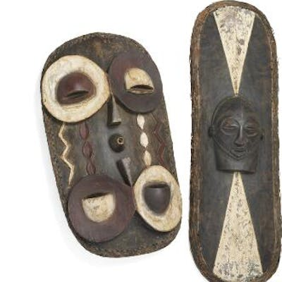 Two shields of carved patinated wood decorated with kaolin